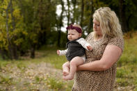 Aubrea Baker and her 7-month-old daughter Haylen visit one of her late husband's favorite fishing spots Saturday, Oct. 2, 2021, in Burlington, Kan. Her husband, Danny Baker, was among the 700,000 U.S. victims of COVID-19, dying on Sept. 14 after testing positive in July. (AP Photo/Charlie Riedel)