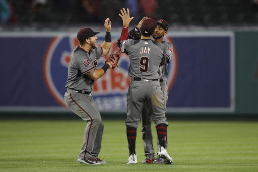 Arizona Diamondbacks' David Peralta, from left, Jon Jay and Jarrod Dyson celebrate the team's 7-4 win against the Los Angeles Angels in a baseball game, Monday, June 18, 2018, in Anaheim, Calif. (AP Photo/Jae C. Hong)