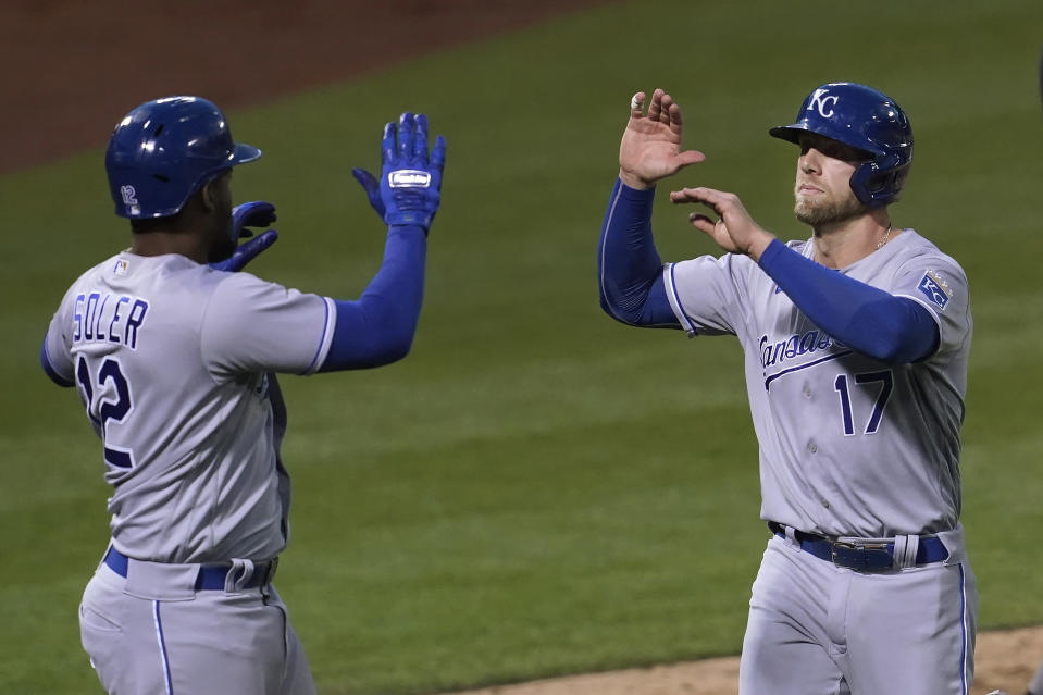 Kansas City Royals' Jorge Soler, left, celebrates with Hunter Dozier after both scored on a two-run single by Kelvin Gutierrez against the Oakland Athletics during the seventh inning of a baseball game in Oakland, Calif., Thursday, June 10, 2021. (AP Photo/Jeff Chiu)