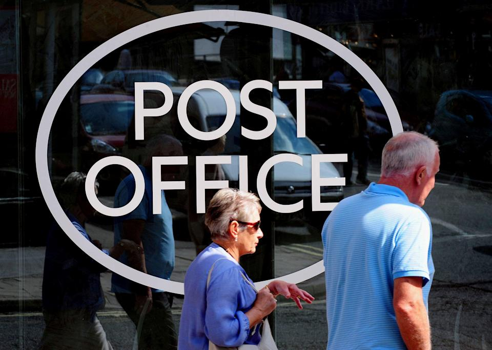 People walk past a Post Office sign (PA Archive)