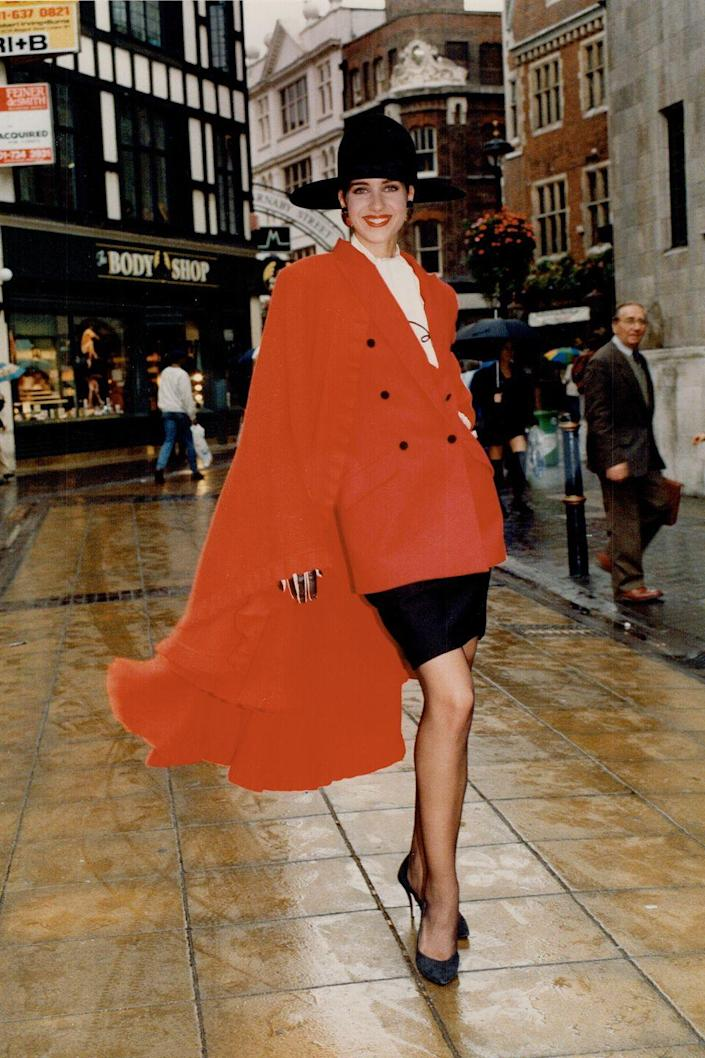 <p>A model wears a cascading red double-breasted blazer, miniskirt, and pumps. </p>