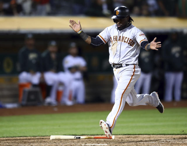 San Francisco Giants' Alen Hanson prepares to step on home plate to score on a double by Hunter Pence during the ninth inning of the team's baseball game against the Oakland Athletics on Saturday, July 21, 2018, in Oakland, Calif. (AP Photo/Ben Margot)