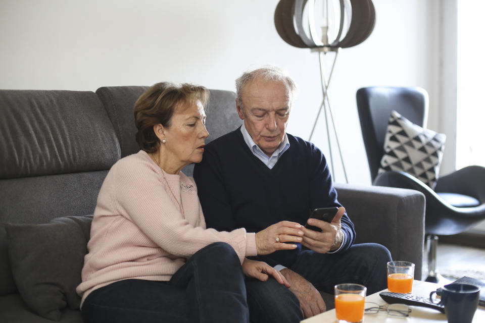 Senior couple in their living room, looking at the phone as government releases coronavirus Whatsapp and iPhone app