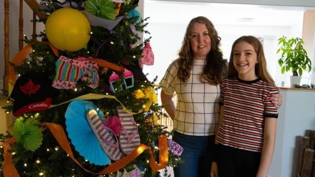 Trisha Lawler and her daughter Charlotte Smyth said they had to get creative with the Victoria Day tree because all the stores are closed during Ontario's stay-at-home order. They decided to go with a summer activity theme and grabbed what they could around the house including flip flops, sunscreen and a bike helmet.  (Jean Delisle/CBC - image credit)