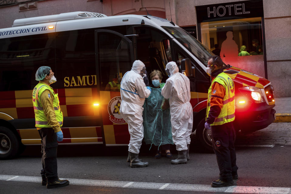 A patient, center, is transferred to a medicalised hotel during the COVID-19 outbreak in Madrid, Spain, Tuesday, March 24, 2020. For most people, the new coronavirus causes only mild or moderate symptoms. For some it can cause a more serious illness. (AP Photo/Bernat Armangue)