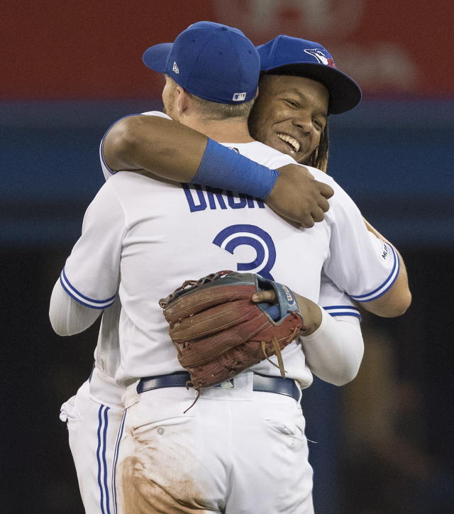 Toronto Blue Jays' Vladimir Guerrero Jr., right, embraces teammate Brandon Drury after they defeated the Texas Rangers in baseball game action in Toronto, Monday, Aug. 12, 2019. (Fred Thornhill/The Canadian Press via AP)