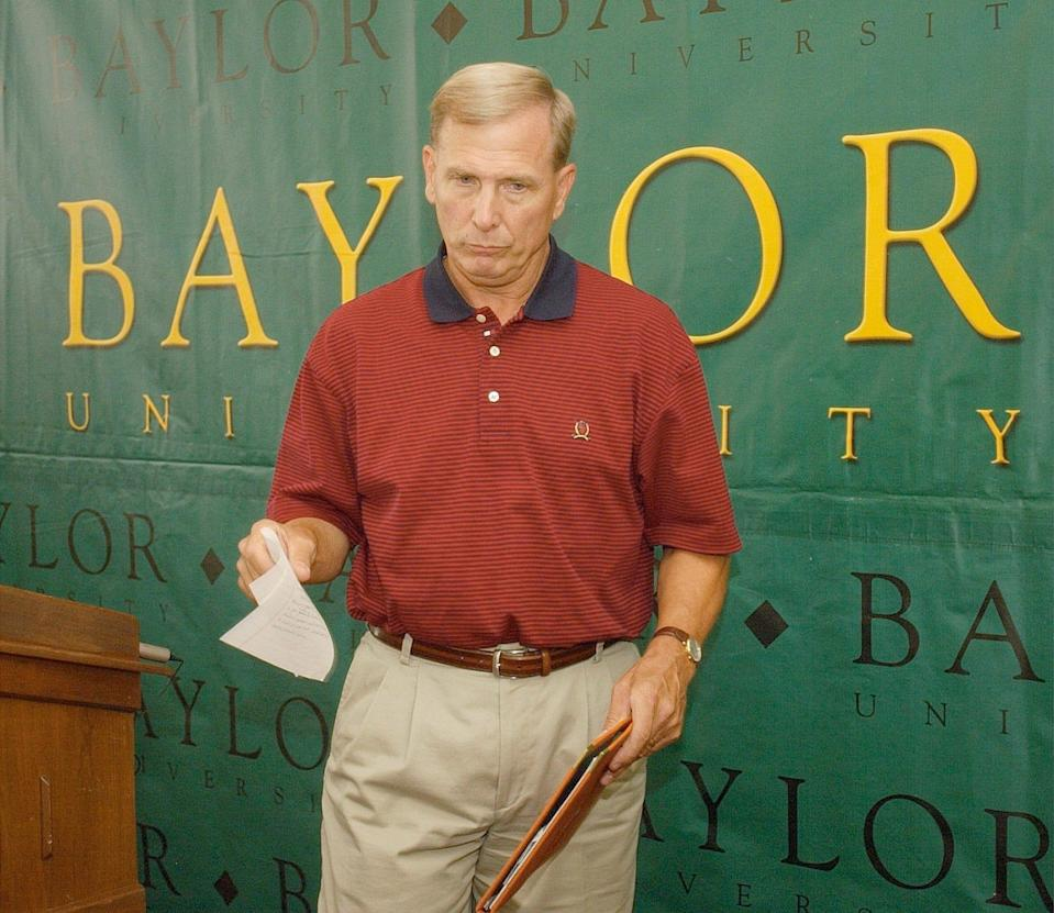 Dave Bliss collects his notes after announcing his resignation as Baylor coach on Aug. 8, 2003.
