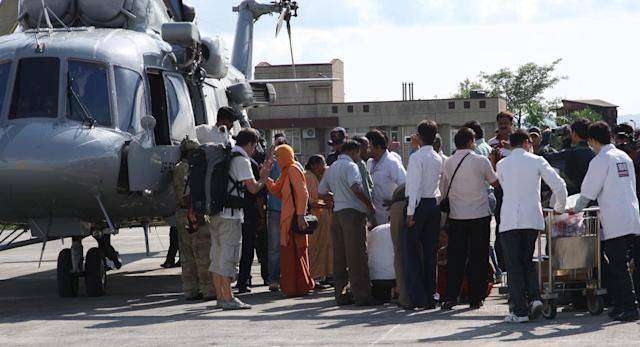 In this handout photograph received from the Ministry of Defence (MOD) on June 27, 2013 rescued people arrive at Jolly Grant airport in Dehradun in the northern Uttarakhand state. Rescue workers stepped up the search for bodies June 27 in India's flood ravaged north, as mass cremations of victims already discovered got underway amid fears of outbreaks of disease , officials and reports said. AFP PHOTO / MOD / NARESH KUMAR