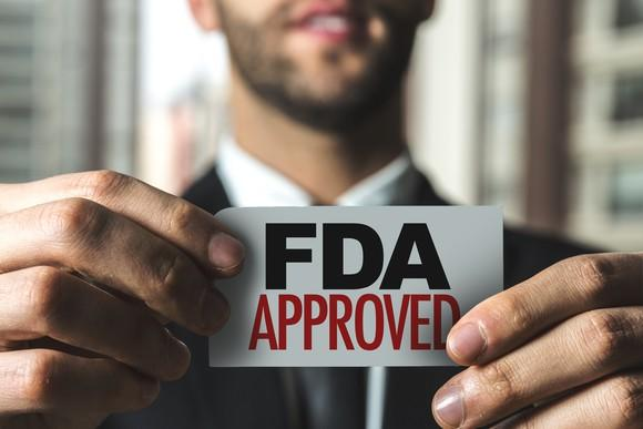 """Businessman holding small card with """"FDA approved"""" printed on it"""