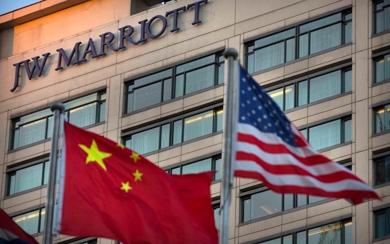 Chinese and American flags fly outside of a JW Marriott hotel in Beijing - AP