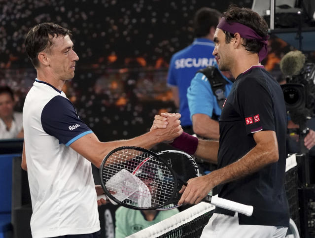 Switzerland's Roger Federer, right, is congratulated by Australia's John Millman after winning their third round match at the Australian Open tennis championship in Melbourne, Australia, Saturday, Jan. 25, 2020.(AP Photo/Lee Jin-man)