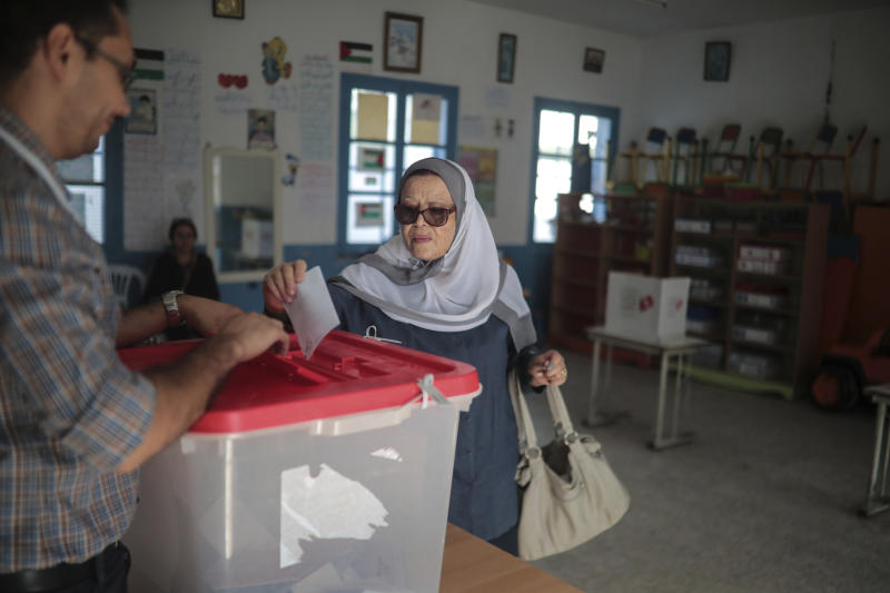 A woman casts her ballot during the second round of the presidential election, in Tunis, Tunisia, Sunday, Oct. 13, 2019. Tunisians are voting for president, choosing between a law professor and populist tycoon. (AP Photo/Mosa'ab Elshamy)
