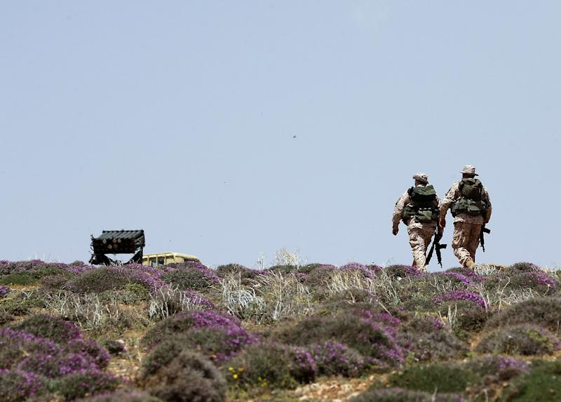 Two Hezbollah fighters patrol a hill on the Lebanese side of the Qalamun mountains on the border with Syria on May 20, 2015