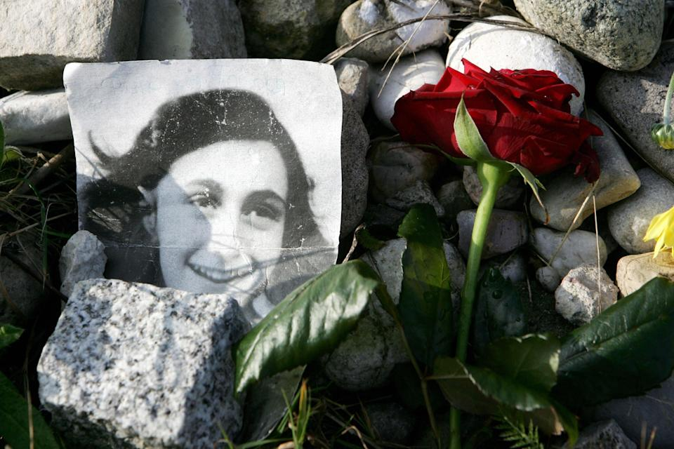 <p>A picture of Anne Frank lies in front of a memorial stone</p> (AFP/Getty)