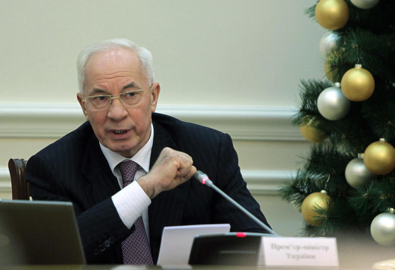 """Ukrainian Prime Minister Mykola Azarov speaks during a cabinet meeting in Kiev, Ukraine, Wednesday, Dec. 18, 2013. Since the mass anti-government protests started in Ukraine about a month ago, both the authorities and the opposition have been waging an information battle in a bid to intimidate, confuse and cajole their opponents, as well as the people of Ukraine. Putin and Yanukovych both pledged Tuesday, Dec. 17, 2013, to boost economic and trade ties to expand the """"strategic partnership"""" between the two neighbors. (AP Photo/Sergei Chuzavkov)"""