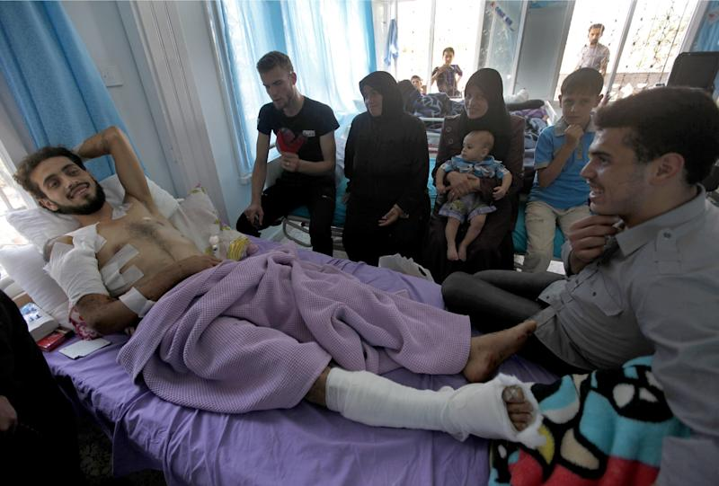 An injured Syrian rebel who identified himself as Abu al-Khatab, 28, who was injured during battle with Syrian troops in Aleppo, visits with family at a safe clinic where rebels can recuperate after surgery in hospitals, in the Turkish-Syrian border town of Kilis, Turkey, Friday, Sept. 21, 2012.(AP Photo/Hussein Malla)