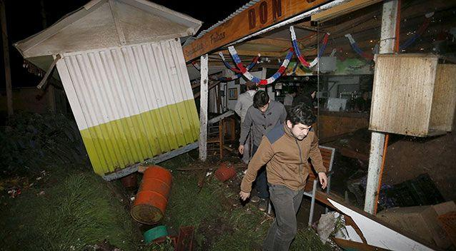 People recover items from a destroyed shop caused by the waves in Concon city, Chile. Photo: Reuters