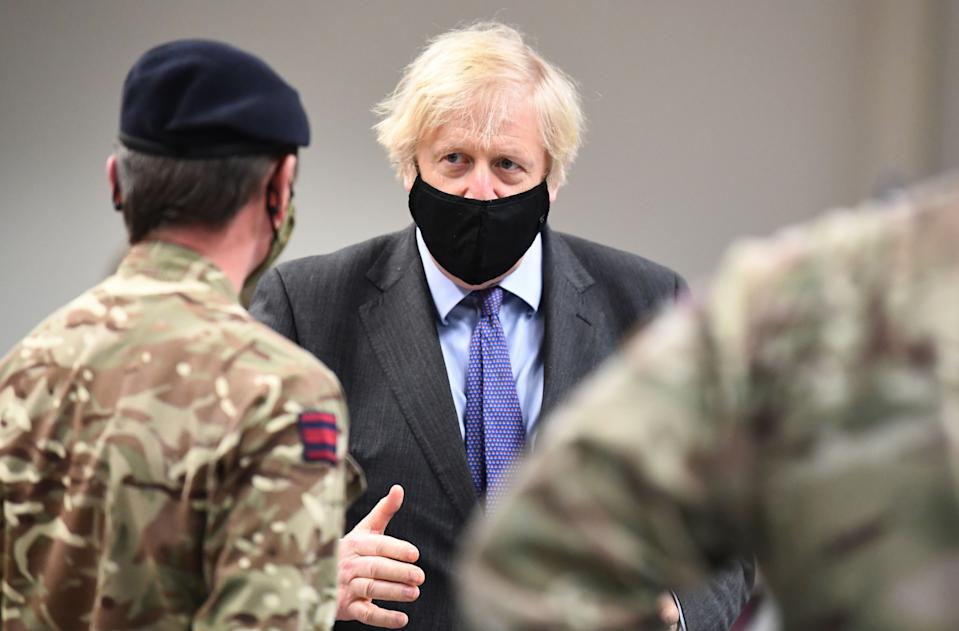 Britain's Prime Minister Boris Johnson meets troops as they set up a vaccination centre in the Castlemilk district in Glasgow, Scotland on January 28, 2021, during a COVID-19 related visit to the country. - Prime Minister Boris Johnson headed to Scotland on Thursday to praise the United Kingdom's collective response to coronavirus, in a bid to counter record support for independence. (Photo by Jeff J Mitchell / POOL / AFP) (Photo by JEFF J MITCHELL/POOL/AFP via Getty Images)