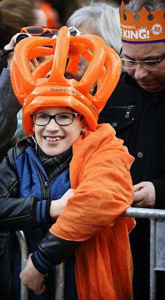 A boy wearing an orange crown waits for the arrival of the royal family members in Tilburg