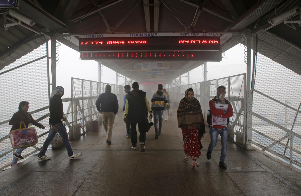<p>People walk on a platform surrounded by dense fog at a train station in Allahabad, India, Jan 6, 2017. Many trains are running behind schedule due to poor visibility caused by fog in north India. (Photo: Rajesh Kumar Singh/AP) </p>