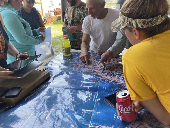 Volunteers gather around a map of the Louisiana coast Thursday, April 29, 2021, in Cocodrie, La., as they search for survivors of the Seacor Power, a lift boat that capsized off the coast on April 13. (AP Photo/Rebecca Santana)