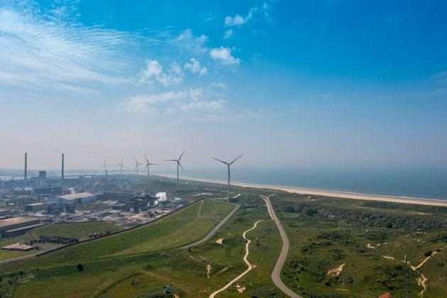 Drone shot of a steel mill in the early morning. Blast furnace and coal depot. Wind turbines near the sea side (Photo: pidjoe via Getty Images)
