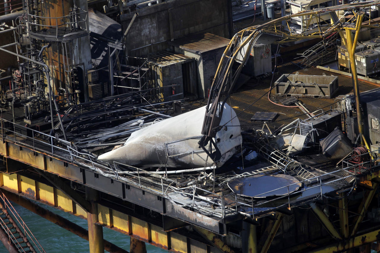 This aerial photograph shows damage from an explosion and fire on an oil rig in the Gulf of Mexico, about 25 miles southeast of Grand Isle, La., Friday, Nov. 16, 2012. Four people were transported to a hospital with critical burns and two were missing. (AP Photo/Gerald Herbert)