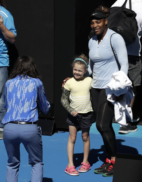 United States' Serena Williams poses for. Photo with a young fan following a practice session at the Australian Open tennis championships in Melbourne, Australia, Sunday, Jan. 13, 2019. (AP Photo/Kin Cheung)