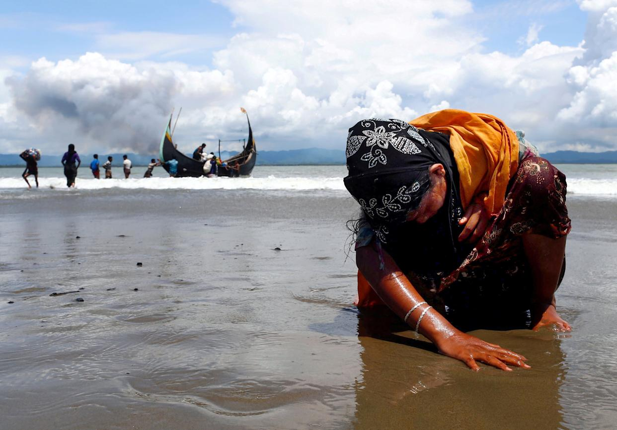 An exhausted Rohingya refugee woman touches the shore after crossing the Bangladesh-Myanmar border by boat through the Bay of Bengal, in Shah Porir Dwip, Bangladesd, on Sept. 11, 2017.