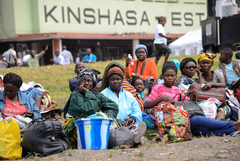 Angolans living in the Democratic Republic of Congo wait with bags at the train station in Kinshasa on August 19, 2014 as ten of thousands prepare to return home