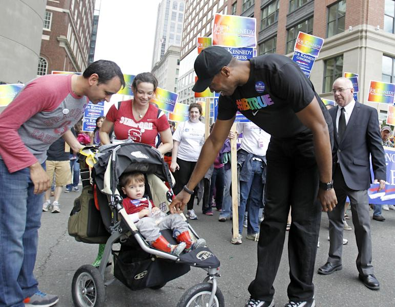 NBA veteran Jason Collins, right, the first active player in one of four major U.S. professional sports leagues to come out as gay, greets a young Stanford fan as he walks in Boston's gay pride parade, Saturday, June 8, 2013, in Boston. (AP Photo/Mary Schwalm)