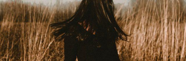 photo of woman standing in field with hair hiding face