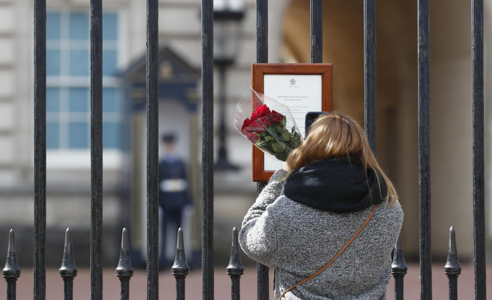 A woman reads the official death notice of Britain's Prince Philip as she prepares to lay flowers at the gate of Buckingham Palace in London, Friday, April 9, 2021. Buckingham Palace officials say Prince Philip, the husband of Queen Elizabeth II, has died. He was 99. (AP Photo/Alastair Grant)