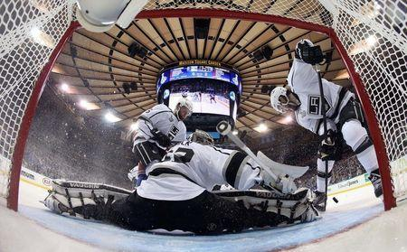 Jun 9, 2014; New York, NY, USA; Los Angeles Kings goalie Jonathan Quick (32) makes a save as defenseman Drew Doughty (right) and defenseman Jake Muzzin (6) try to clear the puck against the New York Rangers during the second period in game three of the 2014 Stanley Cup Final at Madison Square Garden. Mandatory Credit: Bruce Bennett/Pool Photo via USA TODAY Sports