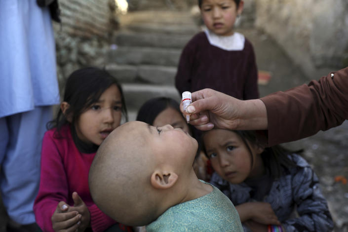 Shabana Maani, gives a polio vaccination to a child in the old part of Kabul, Afghanistan, Monday, March 29, 2021. Afghanistan is trying to inoculate millions of children against polio after pandemic lockdowns stalled the effort to eradicate the crippling disease. But the recent killing of three vaccinators points to the dangers facing the campaign as turmoil grows in the country. (AP Photo/Rahmat Gul)