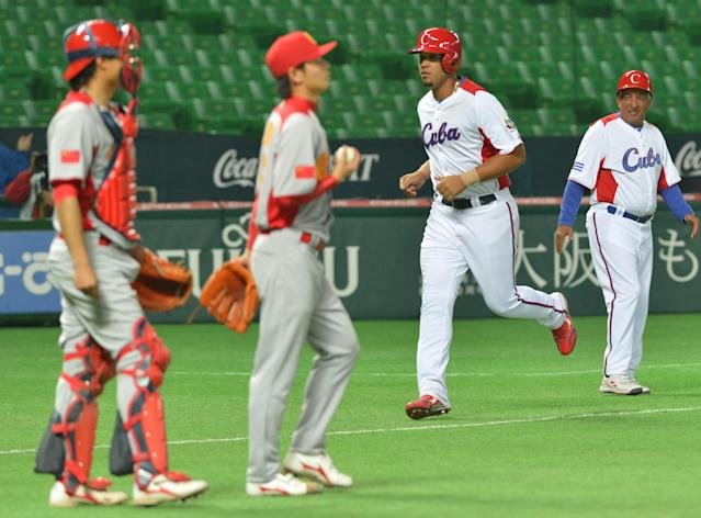 Cuba's Jose Abreu (2nd R) comes into home after hitting a grand slam as China's catcher Meng Weiqiang (L) and pitcher Liu Yu (2nd L) look on during the fifth inning of their first-round Pool A game in the World Baseball Classic tournament in Fukuoka on March 4, 2013. Cuba beat China 12-0 with a called game at the seventh inning. AFP PHOTO / KAZUHIRO NOGIKAZUHIRO NOGI/AFP/Getty Images