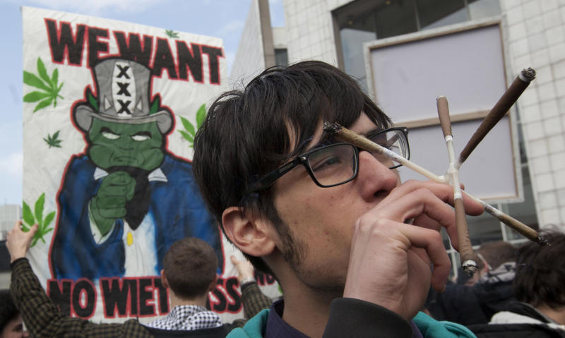 """FILE - In this Friday April 20, 2012 file photo a man smokes five marijuana joints through a contraption with linked tubes in Amsterdam during a protest against a government plan to stop foreigners from buying marijuana in the Netherlands. A Dutch judge has upheld the government's plan to introduce a """"weed pass"""" on Friday, April 27, 2012 to prevent foreigners from buying marijuana in coffee shops. A lawyer for coffee shop owners says he will file an urgent appeal against Friday's ruling that clears the way for the introduction of the pass in southern provinces on May 1. (AP Photo/Peter Dejong, File)"""