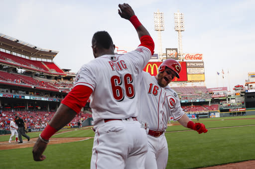 Cincinnati Reds' Tucker Barnhart (16) celebrates with Yasiel Puig (66) after hitting a solo home run off Atlanta Braves starting pitcher Kevin Gausman in the fourth inning of a baseball game, Tuesday, April 23, 2019, in Cincinnati. (AP Photo/John Minchillo)
