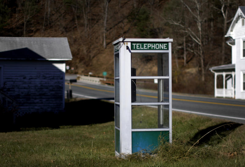 In this Nov. 13, 2013 photo, a phone booth stands on the side of a road in Head Waters, Va., inside the National Radio Quiet Zone. While pay phones have all but disappeared in the United States, they still can be found in this part of the country, where a cell phone signal is hard to come by. The quiet zone, which has been in place since 1958, aims to protect sensitive telescopes at the National Radio Astronomy Observatory, as well as a nearby Naval research facility, from interference created by cell phones and other everyday devices that emit electromagnetic waves. (AP Photo/Patrick Semansky)