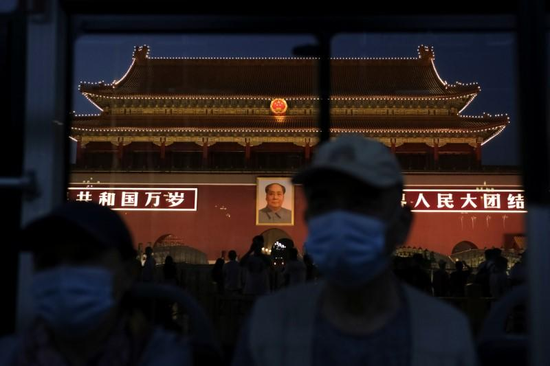 People wearing face masks, following the coronavirus disease (COVID-19) outbreak, ride a bus past  a portrait of late Chinese chairman Mao Zedong on Tiananmen Gate, in Beijing