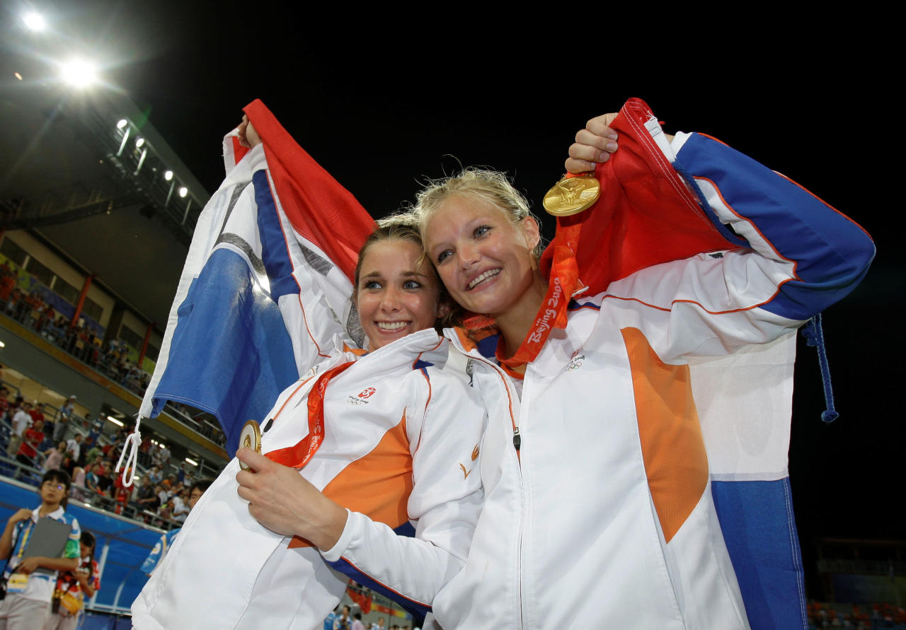 Netherlands' Ellen Hoog, left, and Sophie Polkamp celebrate with their gold medals after defeating China 2-0 in the women's gold medal field hockey match at the Olympic Hockey Center at the Beijing 2008 Olympics in Beijing, Friday, Aug. 22, 2008. (AP Photo/Rick Rycroft)