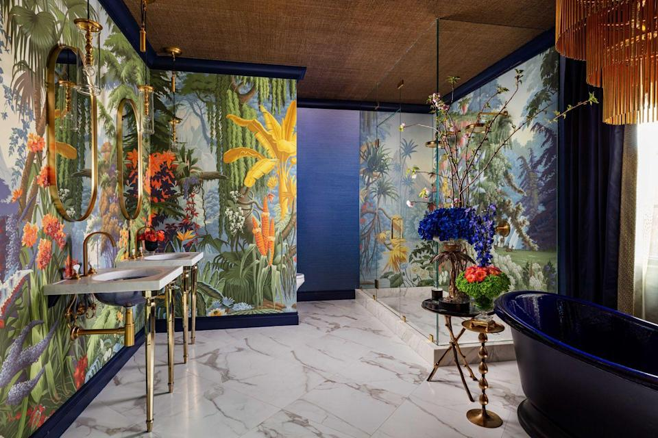 <p><strong>News flash: Bathtubs don't have to be white.</strong> The indigo Kohler tub was the jumping-off point for this bold bathroom, whose colorful de Gournay wallpaper picks up the tub's rich tones and gives the effect of an underwater seascape. The final dramatic effect? A gold raffia on the ceiling. Quite the view for a relaxing soak. </p>