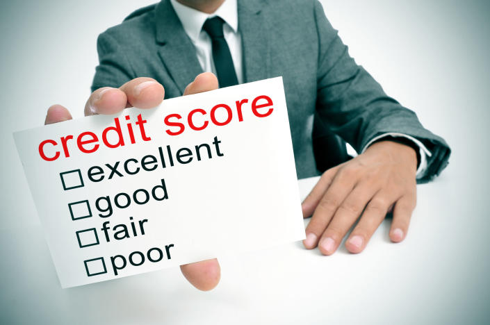 Man in a business suit holding a card reading credit score with check boxes beside excellent, good, fair, and poor.