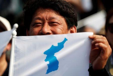 A man displays the Korean unification flag as he watches a news report on the inter-Korean summit, near the demilitarized zone separating the two Koreas, in Paju, South Korea, April 27, 2018. REUTERS/Kim Hong-ji