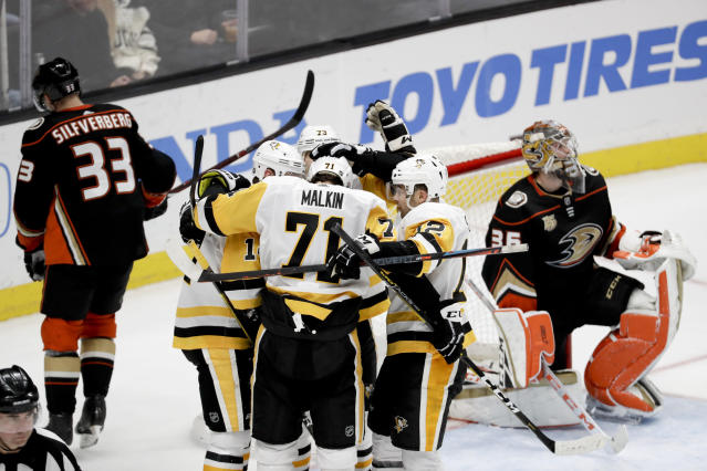 The Pittsburgh Penguins celebrate after a goal by left wing Tanner Pearson past Anaheim Ducks goaltender John Gibson, right, and Jakob Silfverberg, left, during the third period of an NHL hockey game in Anaheim, Calif., Friday, Jan. 11, 2019. The Penguins won 7-4. (AP Photo/Chris Carlson)