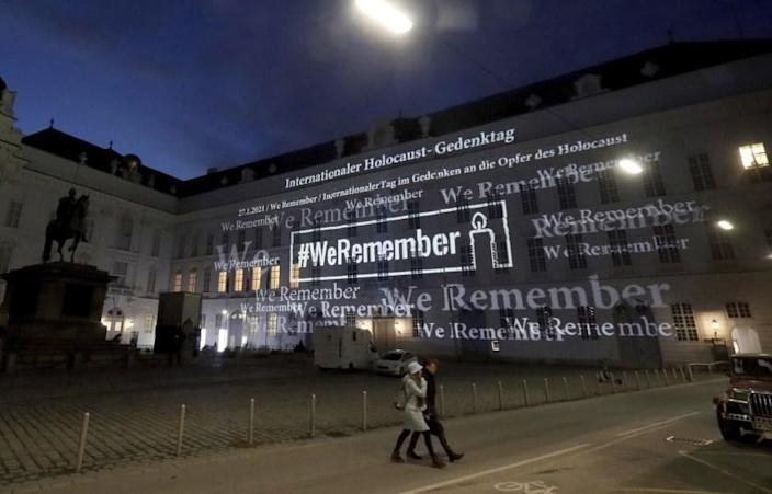 The words '#WeRemember' are displayed at the facade of the Austrian Parliament at the Hofburg palace in support of the campaign for the International Holocaust Remembrance Day in Vienna, Austria, Wednesday, Jan. 27, 2021. The anniversary of the liberation of the Nazi death camp Auschwitz is on Jan. 27, marking the International Holocaust Remembrance Day. (AP Photo/Ronald Zak)