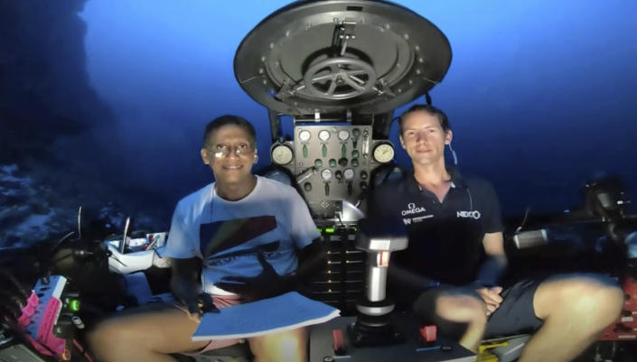 An image taken from video issued by Nekton shows Seychelles President Danny Faure, left, smiling after speaking from inside a submersible from the vessel Ocean Zephyr, under the water off the coast of Desroches, in the outer islands of Seychelles Sunday April 14, 2019. Faure toured the vessel and was presented with some of the findings and observations made by a British-led science expedition documenting changes taking place beneath the waves that could affect billions of people in the surrounding region over the coming decades (Nekton via AP)