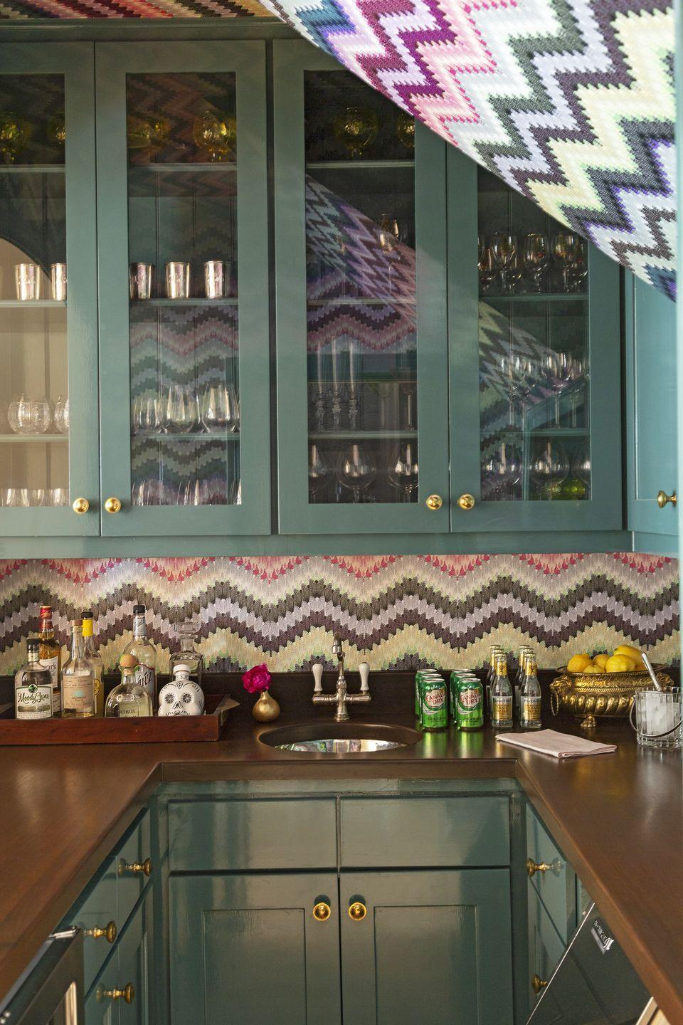 "<p>Bold teal cabinetry (Nocturnal Sea by <a href=""https://www.prattandlambert.com/"" rel=""nofollow noopener"" target=""_blank"" data-ylk=""slk:Pratt & Lambert"" class=""link rapid-noclick-resp"">Pratt & Lambert</a>) and exuberant zig-zag wallpaper (<a href=""https://www.timorousbeasties.com/"" rel=""nofollow noopener"" target=""_blank"" data-ylk=""slk:Timorous Beasties"" class=""link rapid-noclick-resp"">Timorous Beasties</a>) make quite the statement in this home bar by <a href=""https://www.veranda.com/decorating-ideas/house-tours/a34883406/angie-hranowsky-austin-house-tour/"" rel=""nofollow noopener"" target=""_blank"" data-ylk=""slk:Angie Hranowsky"" class=""link rapid-noclick-resp"">Angie Hranowsky</a>, but it's the carefully curated trays that are catching our eyes on this pass. The owner's most-used elixirs are within easy reach without cluttering the countertop thanks to stylish bar trays and antique bowls. </p>"