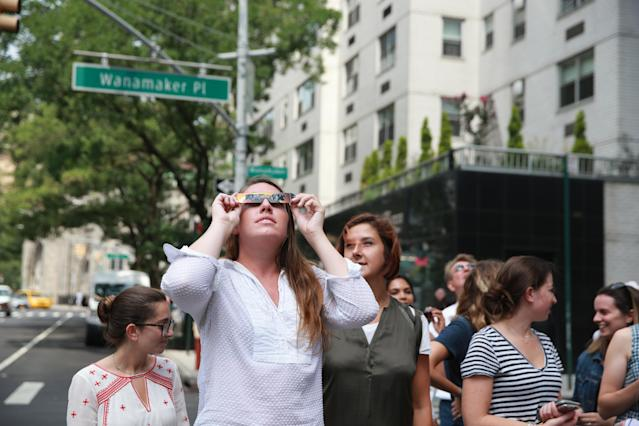 <p>People take a break from work to witness the solar eclipse on Broadway in New York City on Aug. 21, 2017. (Gordon Donovan/Yahoo News) </p>