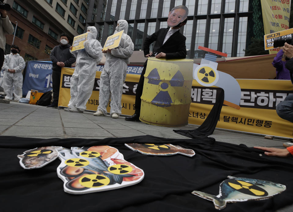 Environmental activists wearing a mask of Japanese Prime Minister Yoshihide Suga and protective suits perform to denounce the Japanese government's decision on Fukushima water, near the Japanese embassy in Seoul, South Korea, Tuesday, April 13, 2021. Japan's government decided Tuesday to start releasing massive amounts of treated radioactive water from the wrecked Fukushima nuclear plant into the Pacific Ocean in two years - an option fiercely opposed by local fishermen and residents. (AP Photo/Lee Jin-man)